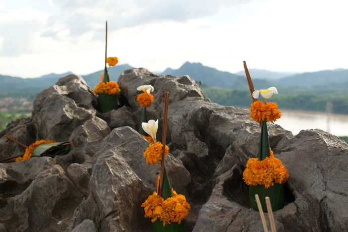 Offerings of flowers and incense on the summit of Phou Si